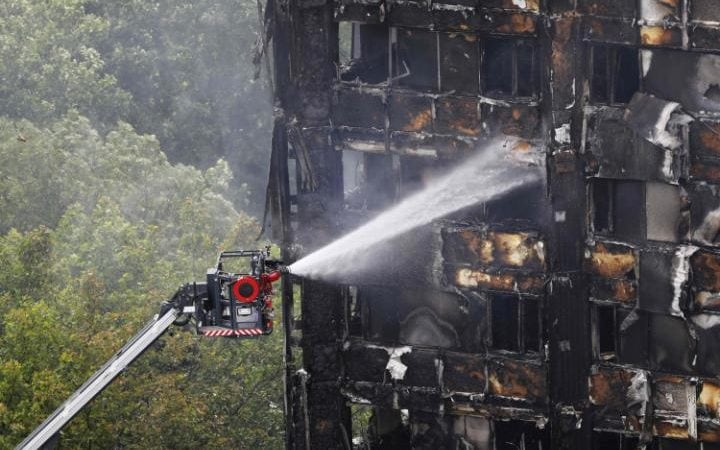 An automated hose sprays water onto Grenfell Tower