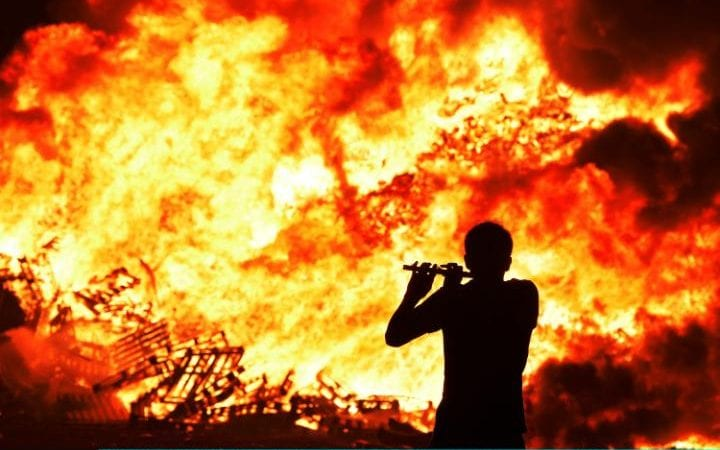 An Orange bandsman plays his flute during the 11th night bonfire at the Belfast New Mossley housing estate in 2015