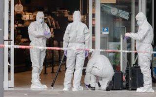Police investigator work at the area around the supermarket