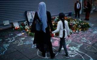 Mourners gather to pay their respects outside the Edeka supermarket