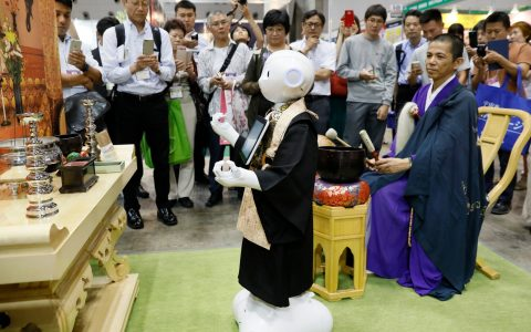 Pepper, a robot developed by SoftBank Corp, takes a part in a demonstration of funeral ceremony with a Buddhist priest at the Tokyo International Funeral and Cemetery Show 2017