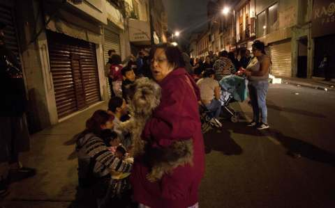People gather on a street in downtown Mexico City during an earthquake