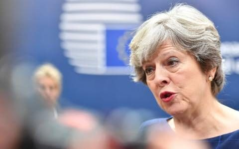 British Prime Minister Theresa May speaks with the media as she arrives for an EU summit in Brussels on Thursday, Oct. 19, 2017