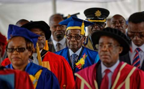 Zimbabwe's President Robert Mugabe, center, arrives to preside over a student graduation ceremony at Zimbabwe Open University on the outskirts of Harare, Zimbabwe