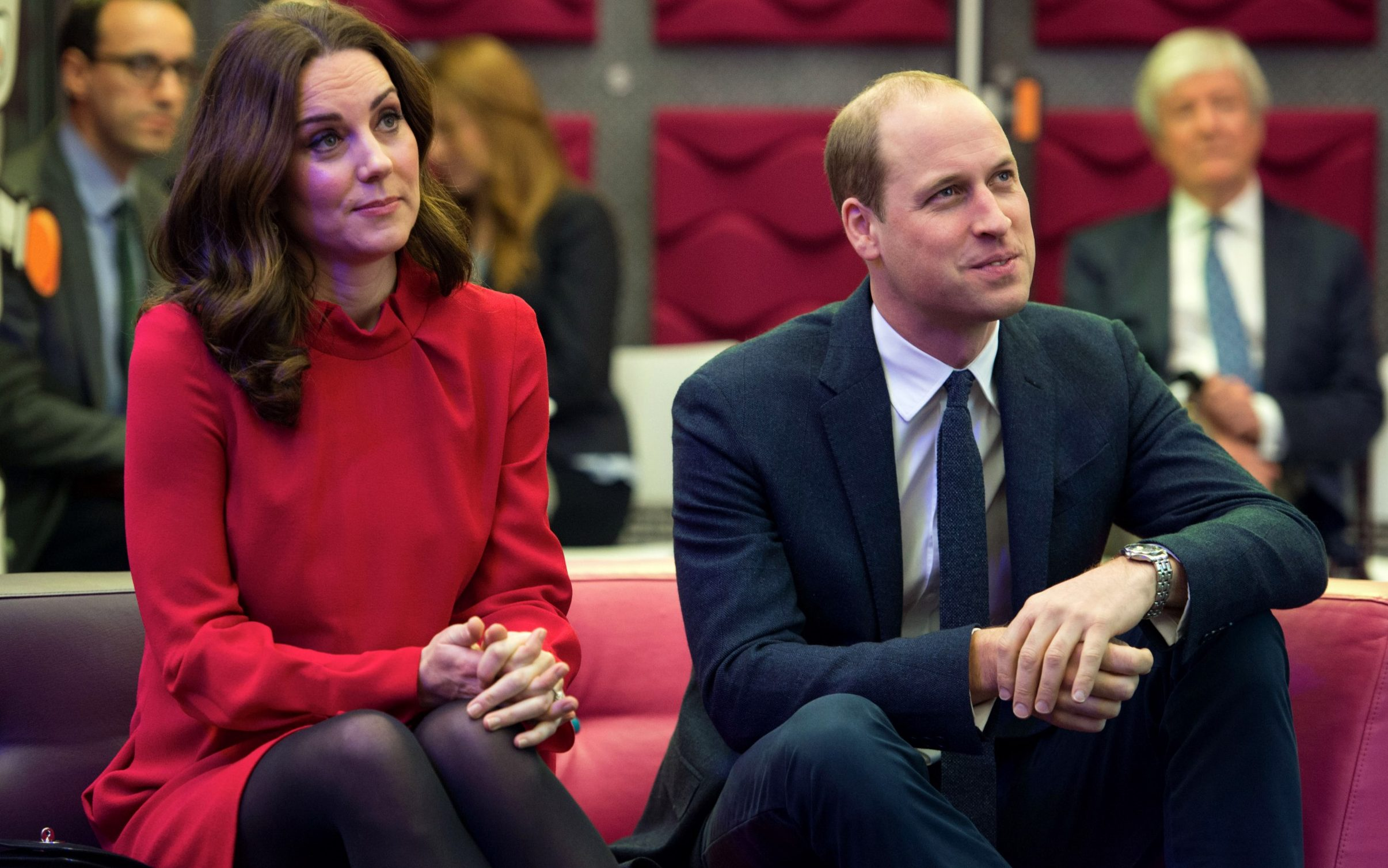 The Duke and Duchess of Cambridge listen to a presentation before speaking to school children