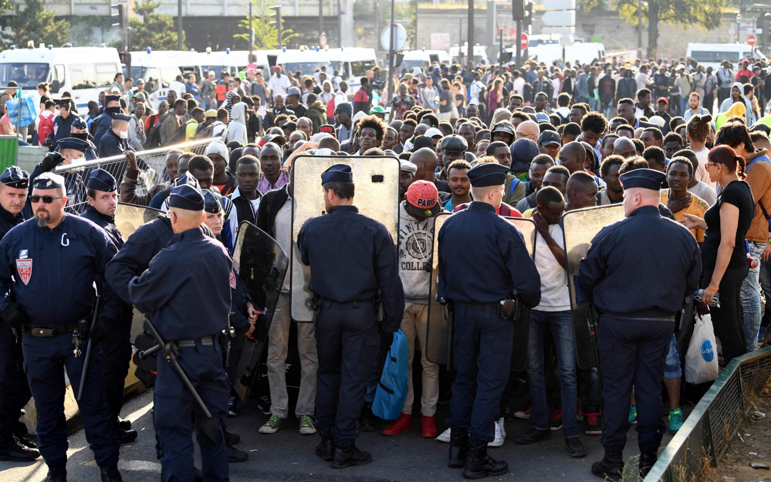 Parisians threaten hunger strike over migrant street camps Riot police stand guard during the evacuation of a makeshift camp in Porte  de la Chapelle