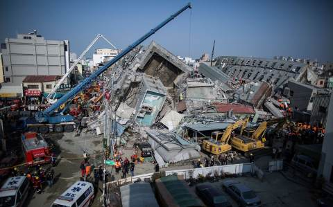 Rescue workers search for victim at a collapsed building on February 7, 2016 in Tainan