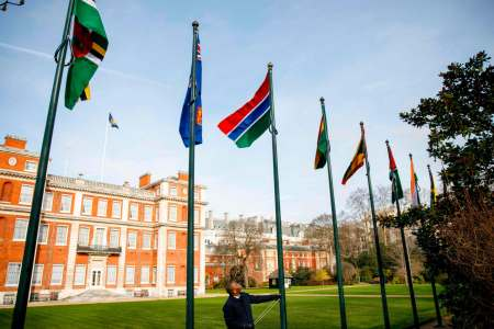 The Gambian flag is raised into position with the other flags of the Commonwealth during a ceremony to officially welcome Gambia back into the Commonwealth