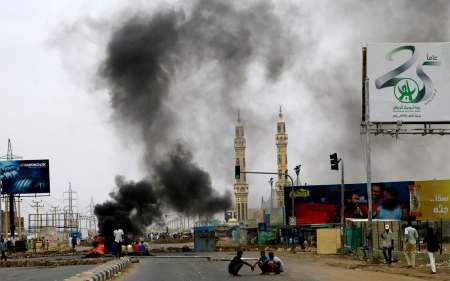 Sudanese protesters are seen near burning tyres used to erect a barricade on a street following the crackdown