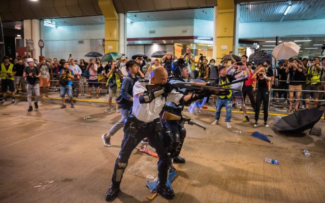 A Hong Kong riot police officer holds a shotgun towards protesters during a demonstration on Tuesday