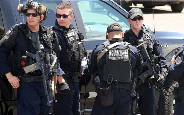 U.S. Customs and Border Protection officers gather near the scene of a shooting at a shopping mall in El Paso