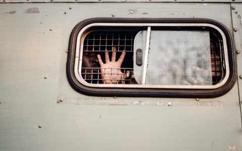 A supporter of the opposition MDC Alliance gestures the party's symbol from inside of a prison truck