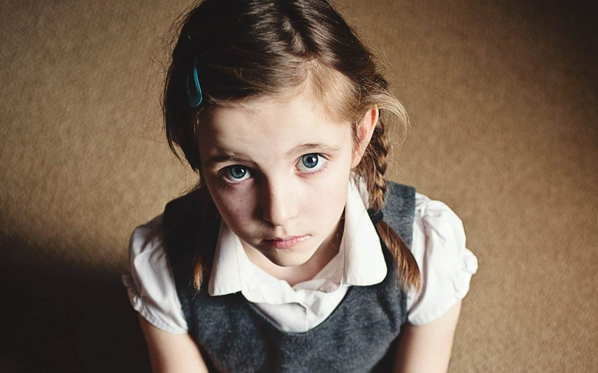 This is a picture of a sad/unhappy looking 7 year old girl. The photo is taken from above and she is sat cross legged on the floor. She is wearing school uniform with pink tights. She has a toy in her hand. She looks lonely. She has plaits in her hair.