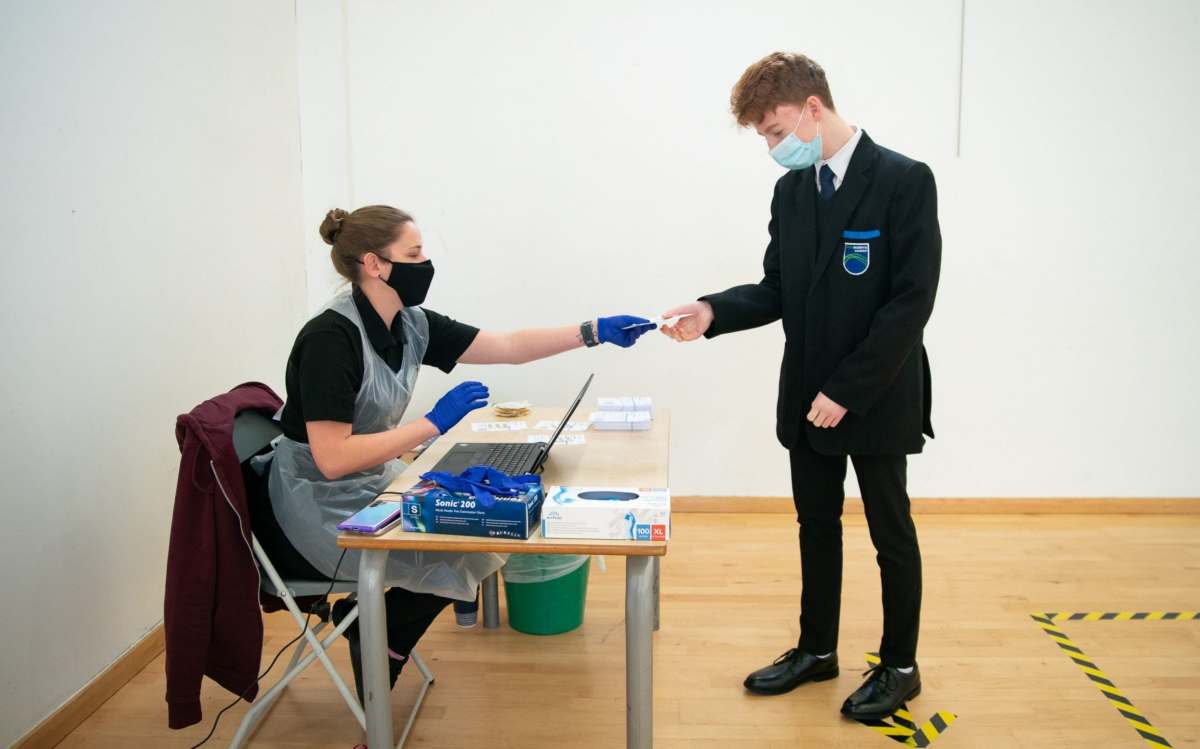 Henry Parker receives instructions on how to take a COVID-19 test at Oasis Academy in Coulsdon, Surrey, where children of key workers and vulnerable children are tested on arrival to ensure a safe return to the school.