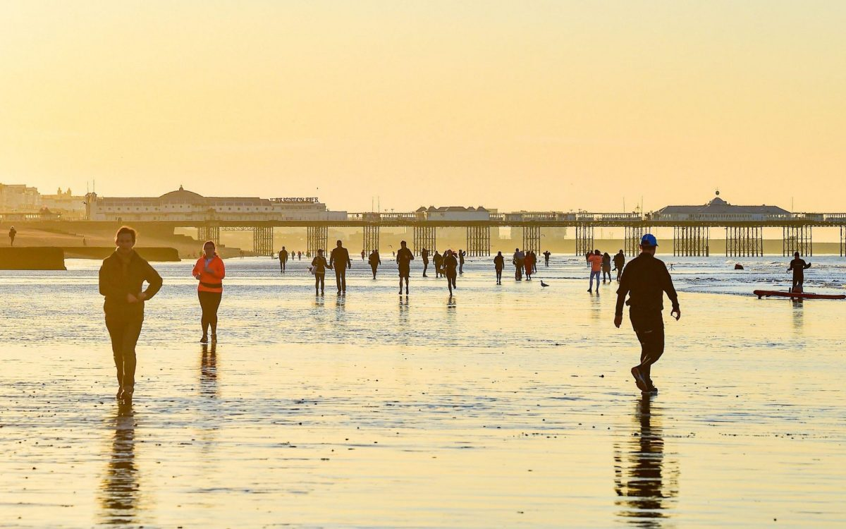 As the stay at home advice was ditched, morning walkers , paddle boarders and swimmers make the most of the extra low tide in Brighton on a beautiful sunny morning along the south coast