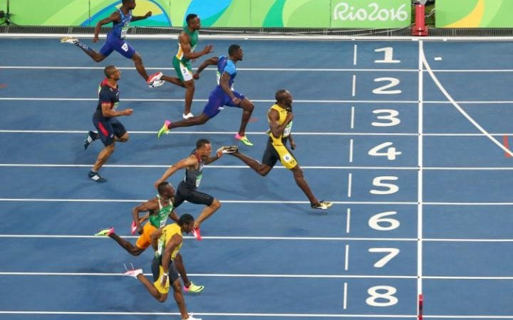 Usain Bolt starts celebrating as he crosses the finish line