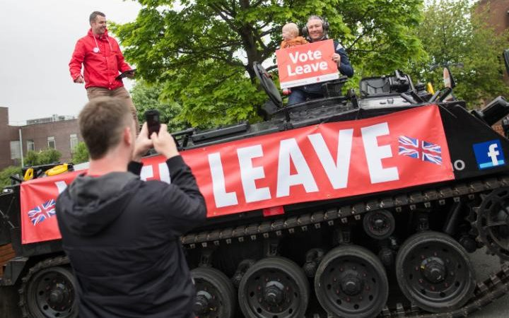 "Jaime Gray uses a smartphone to take a photograph of his 13-month-old son Robert with a ""Vote Leave"" placard on a FV432 modified armored personnel carrier, in the Southwick district of Sunderland, U.K., on Saturday, June 4, 2016."