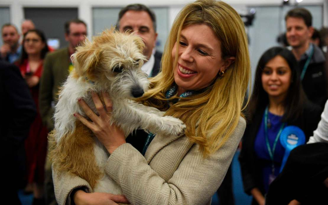 Carrie Symonds, partner of Britain's Prime Minister and Conservative leader Boris Johnson, holds their dog