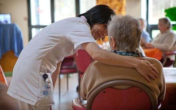 A man with dementia is comforted by a nurse in a care home