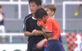 A player sobs into his shirt