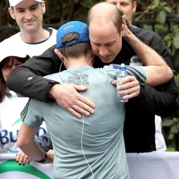 The Duke of Cambridge hugs a runner as he hands out water