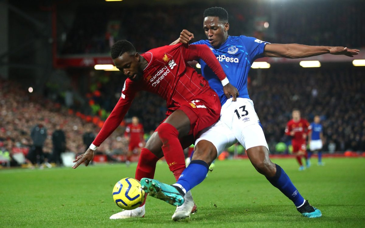 Divock Origi of Liverpool battles for possession with Yerry Mina of Everton in the Premier League in December