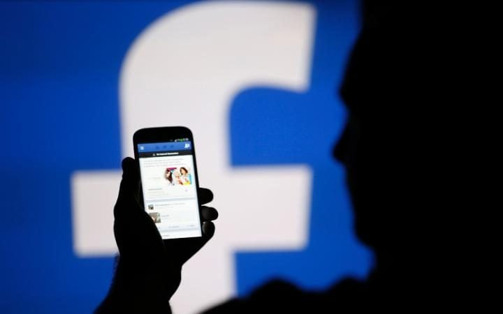 Silhouette of a person using the Facebook app in front of the Facebook logo