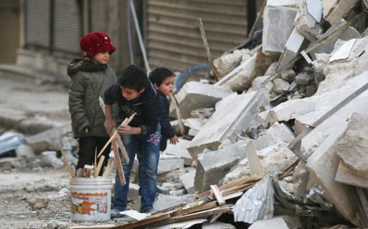 Children collect firewood amid the rubble of Aleppo this week