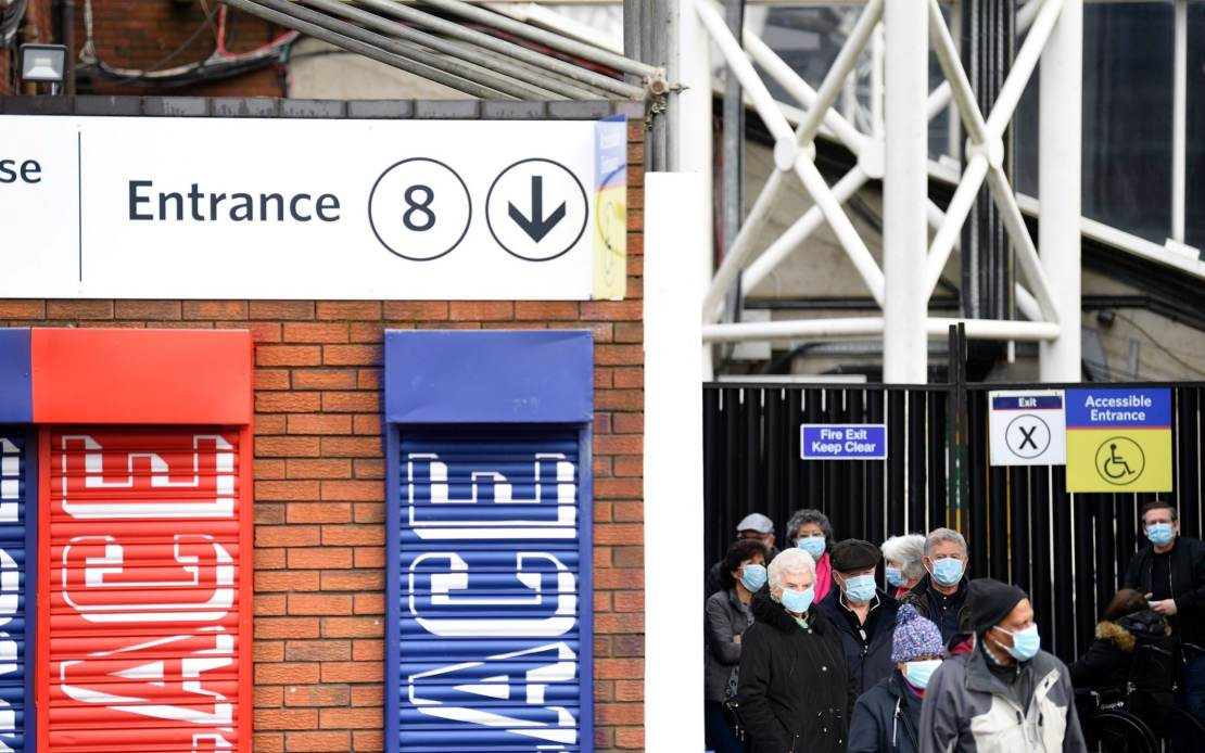 Members of the public wait in a queue to receive a dose of a Covid-19 vaccination, at a temporary centre set up at Selhurst Park football stadium, home ground of English Premiere League football team Crystal Palace, in Croydon