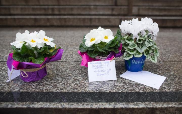 "Flowers with messages reading:  ""you don't hit people even with flowers"" pictured on the steps around the main train station in Cologne"