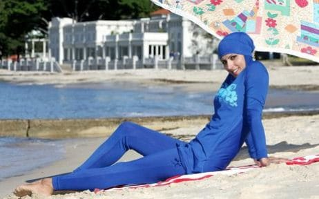 A burkini (full-bodied swimsuit) clad woman on a beach