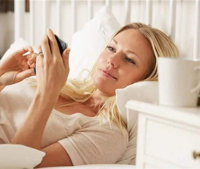 Woman In Bed With Phone Dating Increasingly Takes Place Online