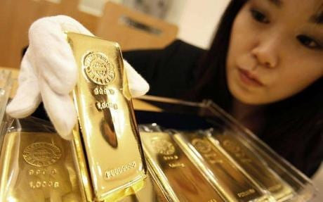 woman with gold bar - Citigroup says gold could rise above $2,000 next year as world unravels