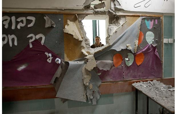 An Israeli man looks at a classroom damaged after a rocket landed in the school in the southern city of Beersheba