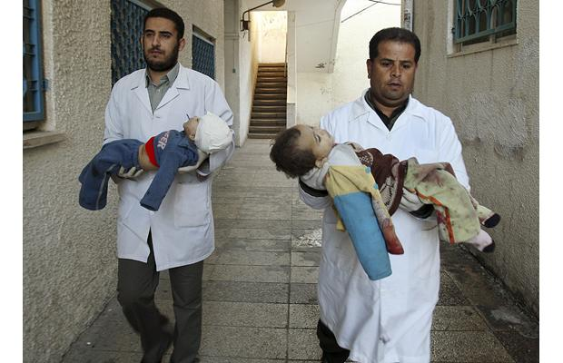 Palestinian doctors carry the bodies of children killed by an Israeli tank shell, to the morgue at Shifa hospital in Gaza