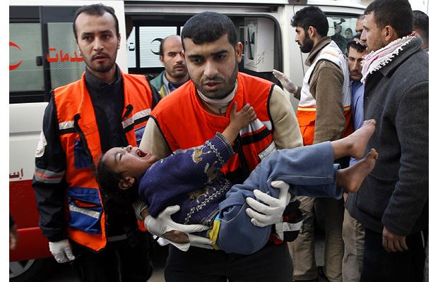 A Palestinian medic carries an injured child into Kamal Adwan Hospital in Beit Lahiya, northern Gaza Strip
