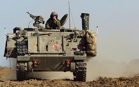An Israeli soldier looks out from atop an armoured personnel carrier near the border with the northern Gaza Strip