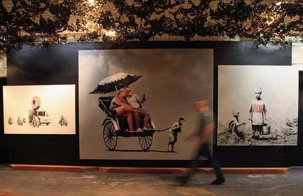 A man passes some the recognisable stencil artworks of Banksy