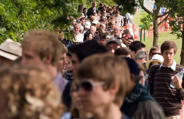 Spectators queue in fields opposite the club before the public gates are opened on the second day of the Wimbledon Tennis Championships, west London on June 23, 2009.