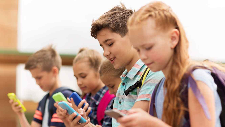 Grupo de niños mirando sus teléfonos móviles