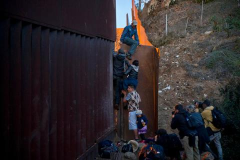 A Honduran migrant helps others to cross the wall between Mexico and the United States.