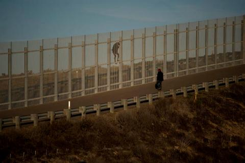 Two migrants try to cross the fence that separates Mexico and the United States.