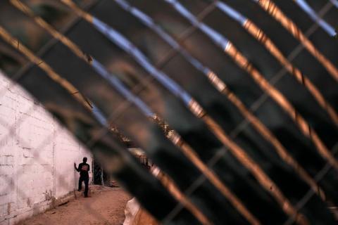 En esta imagen, tomada el 26 de septiembre de 2016, un migrante haitiano espera pegado a una pared del centro de migrantes Padre Chava mientras en el interior se sirve la cena, en Tijuana, México