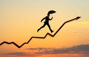TeleSintese-Grafico-positivo-crescendo-seta-aumento-resultado-homem-guarda-chuva-Fotolia_144143619