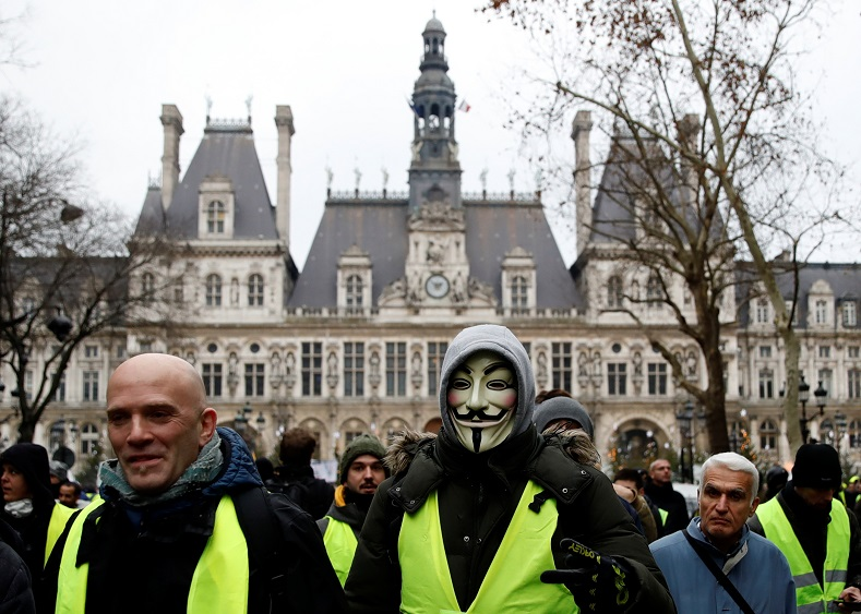 A protester in a yellow vest wearing a Guy Fawkes mask walks near Hotel de Ville in Paris.