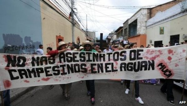 "Resistance group Movimiento Unificado Campesino del Aguan (Unified Campesino Movement of the Aguan) holds a sign that says ""No more murders of campesinos in the Aguan."" (Photo: AFP)"