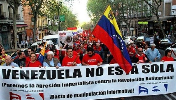 """A banner reads """"Venezuela is not alone"""" on a demonstration in Spain in 2014"""