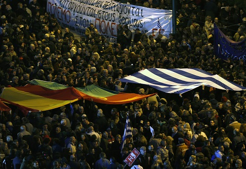 Protesters wave Greek, Portuguese and Spanish flags in front of the parliament during an anti-austerity and pro-government demonstration in Athens February 15, 2015.