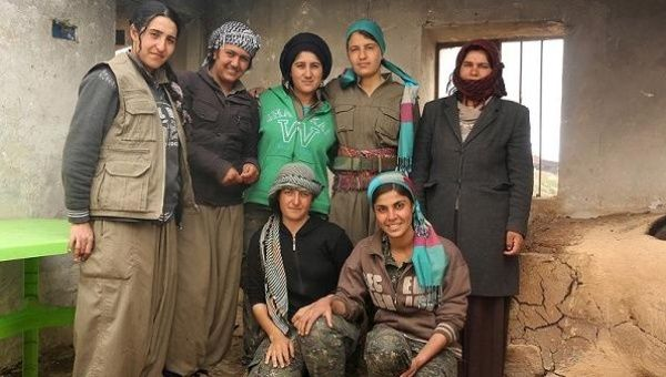 Kurdish Women fighters pose for a picture with a displaced Yazidi woman (R) who lives near the base in Sinjar.