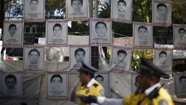 Police stand in front of pictures of the 43 students missing from Ayotzinapa school as their relatives take part in a meeting with Mexico
